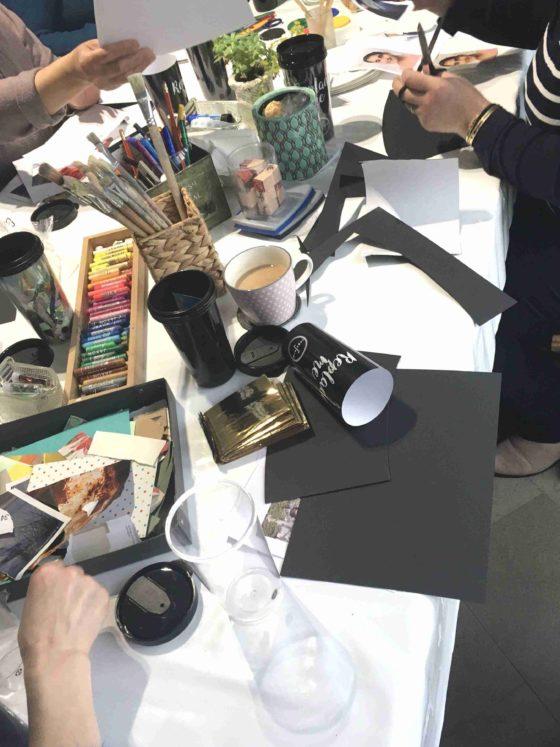 Atelierraum Kunst-Therapie-Hannover (Foto): Tisch mit vielen Materialien und Händen die danach greifen und Papiere halten und schneiden. Hier trifft sich die neue Intervisionsgruppe der Kunsttherapeuten_innen aus der Region Hannover.