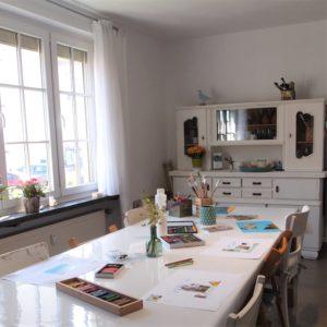 Atelierraum Kunst-Therapie-Hannover (Foto): Im Vorgergrund ein großer Tisch mit Materialien und im Hintergrund links ein Sprossenfenster und rechts eine weiße Kommode. Hier trifft sich die neue Intervisionsgruppe der Kunsttherapeuten_innen aus der Region Hannover.